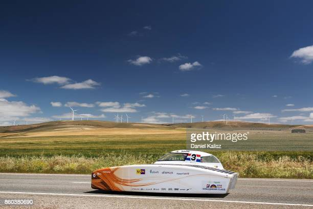 Nuon Solar Team vehicle 'Nuna9' from the Netherlands passes the Snowtown wind farm on Day 5 of the 2017 Bridgestone World Solar Challenge at Redhill...