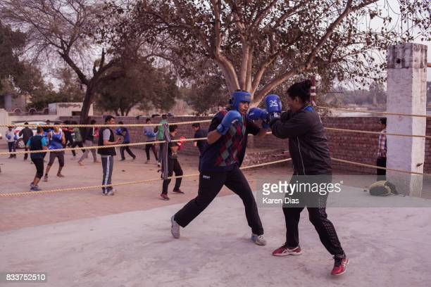 Nupur Sheoran 18 and Pooja Rani Bohra spar in the boxing ring at the Captain Hawa Singh Boxing Academy in the town of Bhiwani There are about 40 boys...