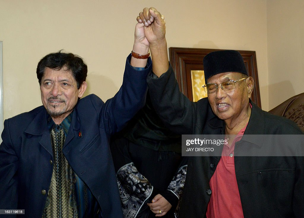 Nur Misuari (L), founding chairman of the Muslim separatist insurgent movement in the Philippines, raises the arm of the self-proclaimed Sultan of Sulu, Jamalul Kiram III (R) during a visit to the ailing sultan's home in Manila on March 5, 2013. Misuari denied he was involved in the incursion of dozens of armed followers of Kiram in the Malaysian state of Sabah in an effort to assert their claim to the area. Meanwhile Kiram said his gunmen would 'fight to the last man' as Malaysian troops mounted an operation to end a deadly three weeks-old stand-off in Sabah on Borneo island. AFP PHOTO / Jay DIRECTO