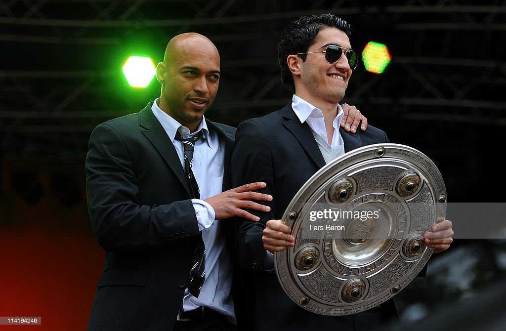 Nuri Sahin holds the trophy next to team mate Dede on the stage during the Borussia Dortmund Bundesliga winners parade at Westfalenhalle on May 15, 2011 in Dortmund, Germany.