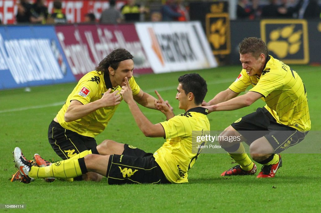 Nuri Sahin (C) of Dortmund celebrates (R) with his team mates Neven Subotic (L) and Lukasz Piszczek after scoring his team's second goal during the Bundesliga match between Borussia Dortmund and FC Bayern Muenchen at Signal Iduna Park on October 3, 2010 in Dortmund, Germany.