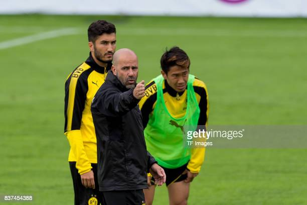 Nuri Sahin of Dortmund Head coach Peter Bosz of Dortmund and Shinji Kagawa of Dortmund looks on during a training session as part of the training...
