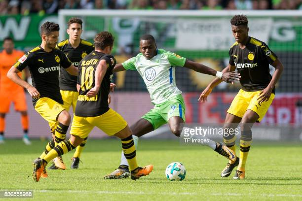 Nuri Sahin of Dortmund Mario Goetze of Dortmund Nany Landry Dimata of Wolfsburg and DanAxel Zagadou of Dortmund battle for the ball during to the...