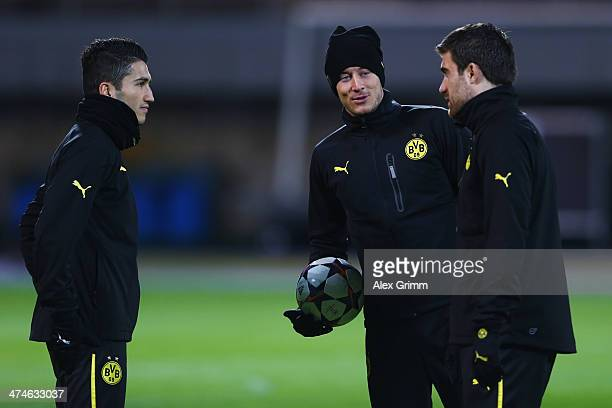 Nuri Sahin Robert Lewandowski and Sokratis Papastathopoulos of Dortmund chat during a training session ahead of the UEFA Champions League Round of 16...