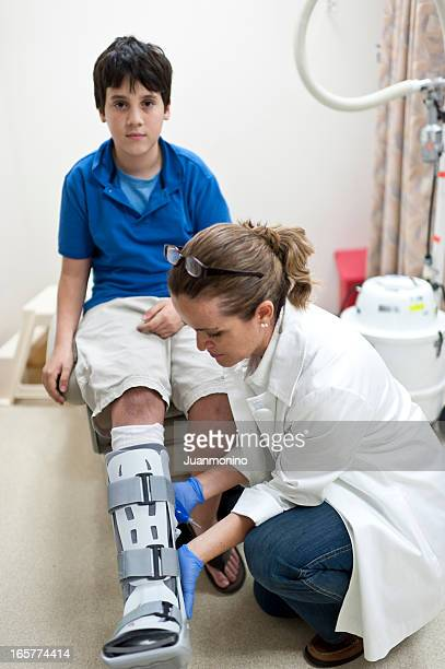 Nurse adjusting orthopedic boot to a child