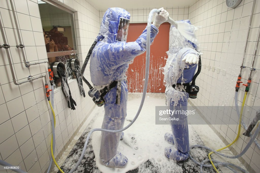 A nurse and a doctor for tropical medicine wearing isolation suits demonstrate the decontamination procedure as part of ebola treatment capability at Station 59 at Charite hospital on August 11, 2014 in Berlin, Germany. The specialized quarantine unit at Station 59 is among a handful of facilities in Germany nationwide that are capable of handling ebola cases. According to media reports a German medical student currently in Ruanda is showing signs of the disease, though should he in fact have ebola it is so far unclear whether he would be flown to Germany for treatment. The disease has so far claimed over 1,000 lives in western Africa in recent weeks.