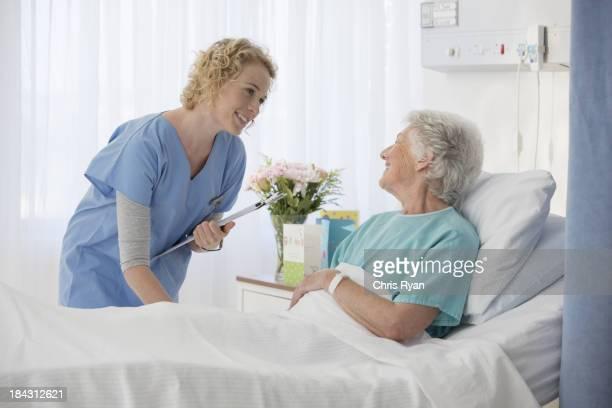 Krankenschwester und aging-Patienten sprechen in Krankenhaus-Zimmer