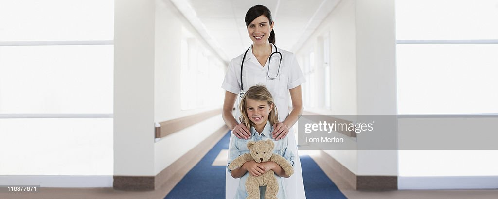 Nurse and child patient with teddy bear in hospital corridor : Stock Photo