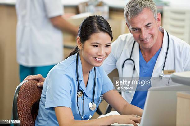 Nurse and doctor using laptop