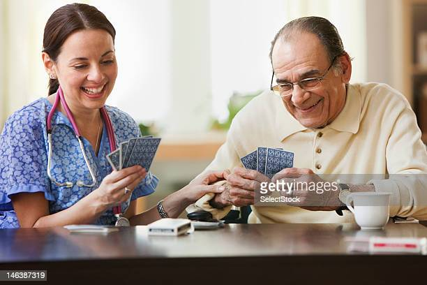 Nurse and elderly man playing cards