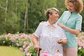 Elderly woman standing with a cane in a garden and looking at her young nurse