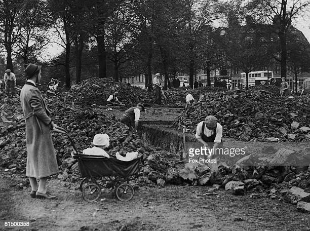 A nurse and her charge watch as workmen dig air raid shelter trenches on Streatham Common south London 27th September 1938