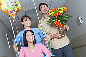 Nurse and man with bouquet assigning woman on wheelchair in hospital hallway