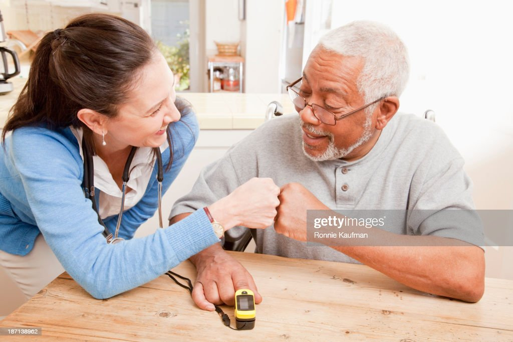 Nurse and older patient cheering in home