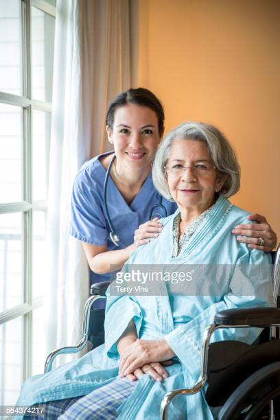 Nurse and older patient in wheelchair smiling near window