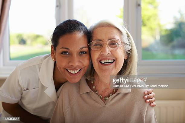 Nurse and older woman smiling together
