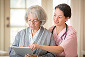 Nurse and patient using digital tablet in home