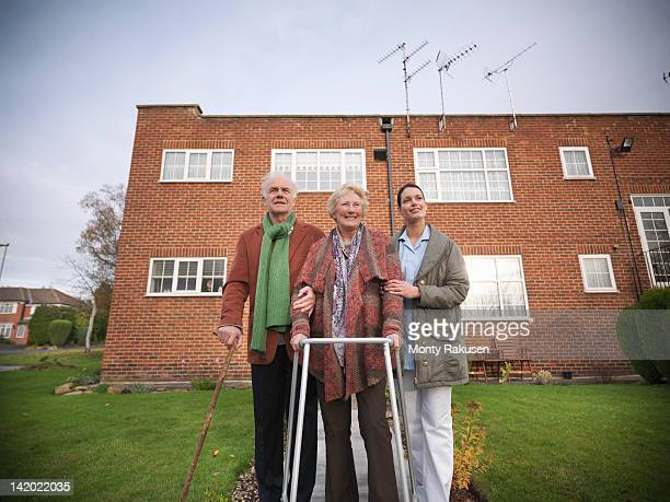 Nurse and senior couple walking in garden