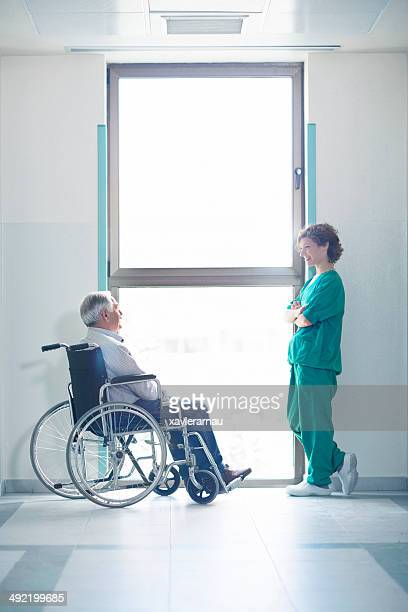 Nurse and senior patient talking in the corridor