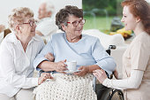Nurse and senior women have fun during conversation in common room