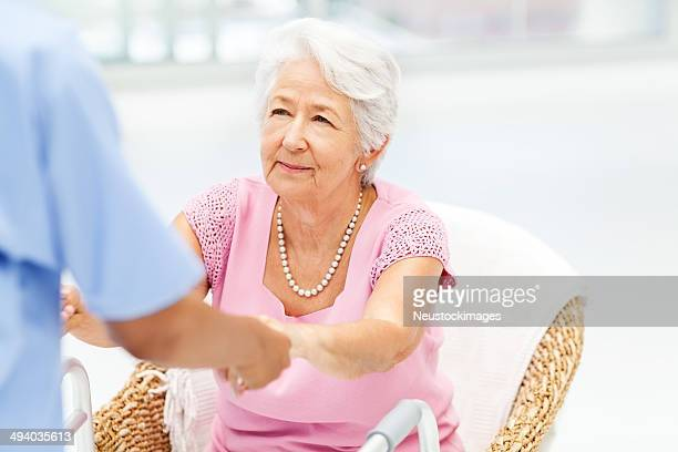 Nurse Assisting Disabled Senior Woman In Getting Up From Chair