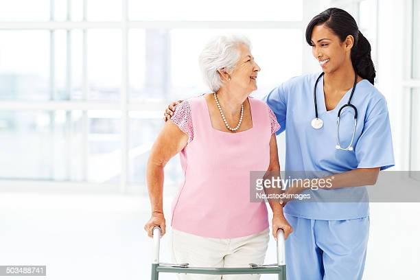 Nurse Assisting Elderly Woman With Walker While Looking At Her