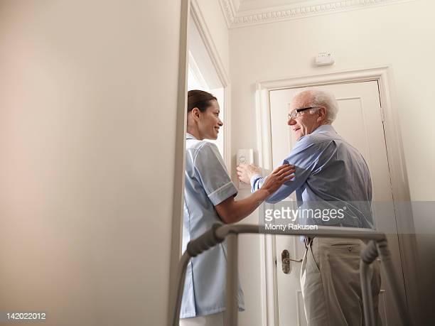 Nurse assisting senior man to adjust thermostat in hallway