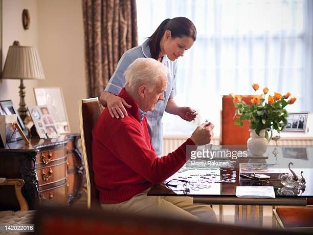 Nurse assisting senior man to complete jigsaw puzzle
