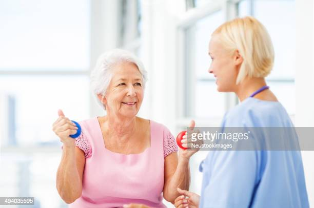 Nurse Assisting Senior Patient In Hand Therapy Balls