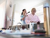 Nurse assisting senior woman to brush hair in bathroom