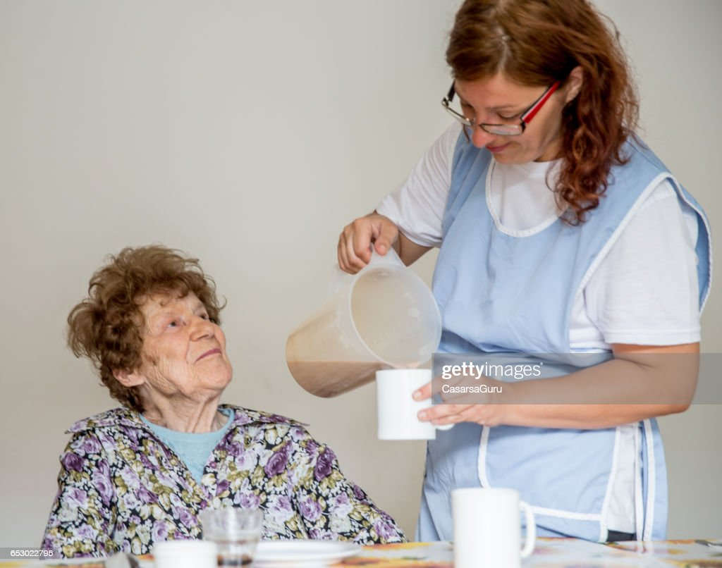 Nurse At The Care Center Serving Breakfast To The Resident : ストックフォト