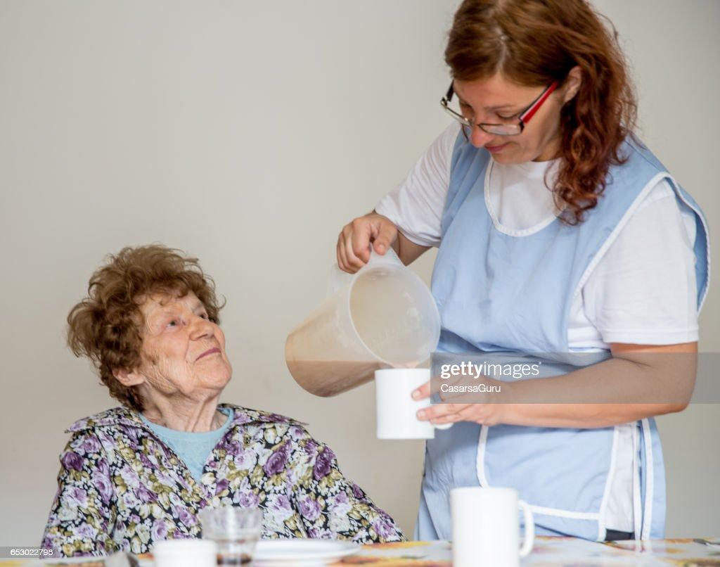Krankenschwester im Pflegezentrum Frühstück an die Einwohner : Stock-Foto