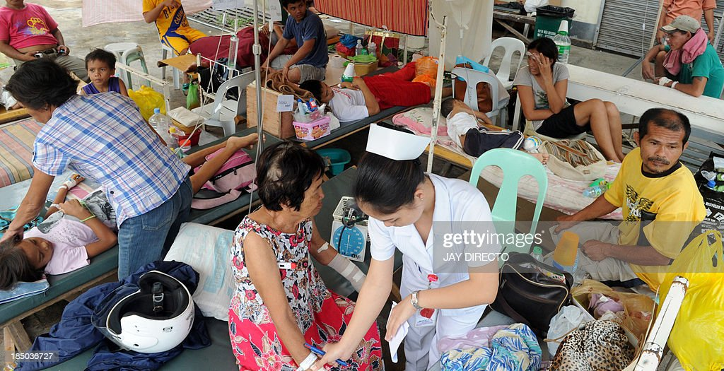 A nurse attends to an elderly woman, one of about 100 injured survivors of a 7.1-magnitude earthquake in a temporary shelter in the parking lot of a government hospital in Tagbilaran city, the capital of Bohol island, on October 17, 2013. The quake struck the central Philippines on October 15, 2013, killing 161 people. AFP PHOTO / Jay DIRECTO