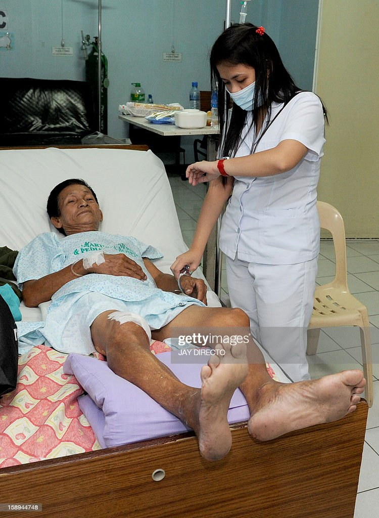 A nurse attends to Raul Ravelo, a victim of a shooting rampage, at a hospital in Kawit, about 40 kms (25 miles) south of Manila on January 4, 2013. The gunman armed with a semi-automatic pistol killed at least five people and wounded 11 others as he rampaged through a slum on the outskirts of the Philippine capital, authorities said. AFP PHOTO / JAY DIRECTO