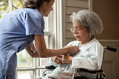 Nurse buttoning shirt of patient in wheelchair near window