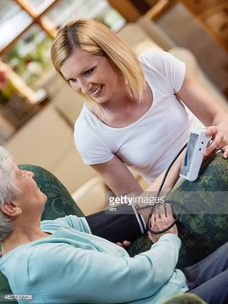 Enfermera de comprobación de la presión arterial de una mujer mayor
