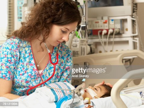 Nurse checking boy in Intensive Care Unit bed : Stock Photo