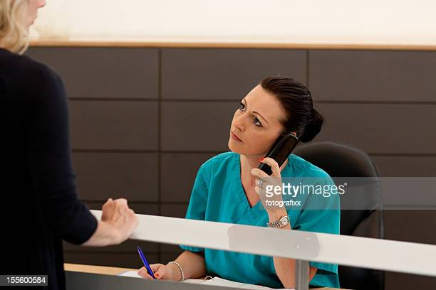 nurse checking in female patient at the reception