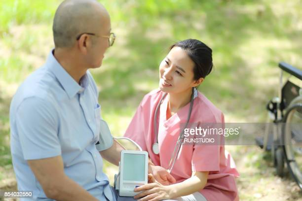 Nurse checking measuring blood pressure