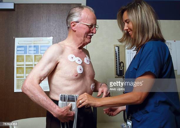 Nurse checking medical equipment on man
