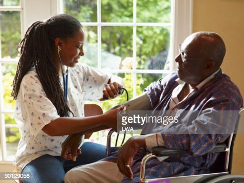 Nurse Checking Patient's Blood Pressure : Stock Photo