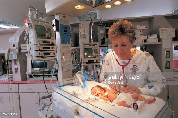 Nurse checking premature baby in intensive care