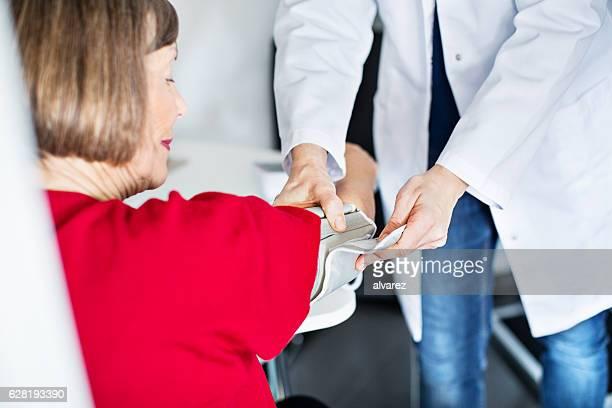 Infirmière vérification de la pression artérielle de la femme âgée