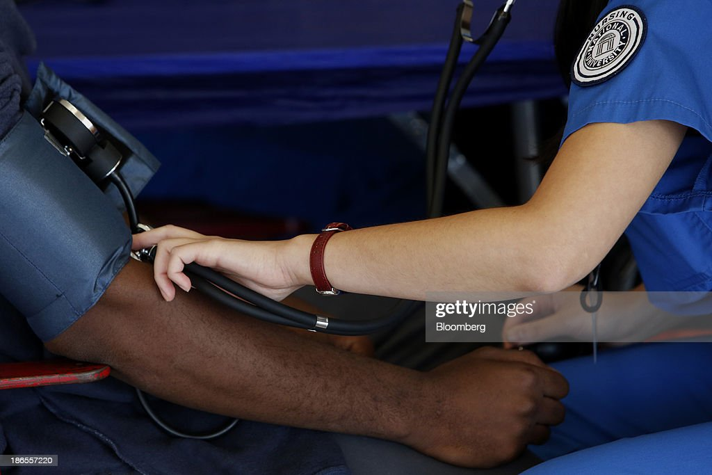 A nurse checks a patient's blood pressure during the Care Harbor Public Health Clinic event at the Los Angeles Sports Arena in Los Angeles, California, U.S., on Thursday, Oct. 31, 2013. The rate of uninsured Americans dropped slightly for the second consecutive year in 2012, a result of more people enrolling in Medicare and Medicaid, the U.S. Census Bureau reported Tuesday. Photographer: Patrick Fallon/Bloomberg via Getty Images