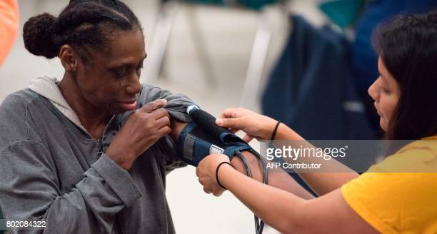 A nurse checks the blood pressure of a patient at Greensville County High School in Emporia Virginia on June 25 receiving free medical aid by Remote...