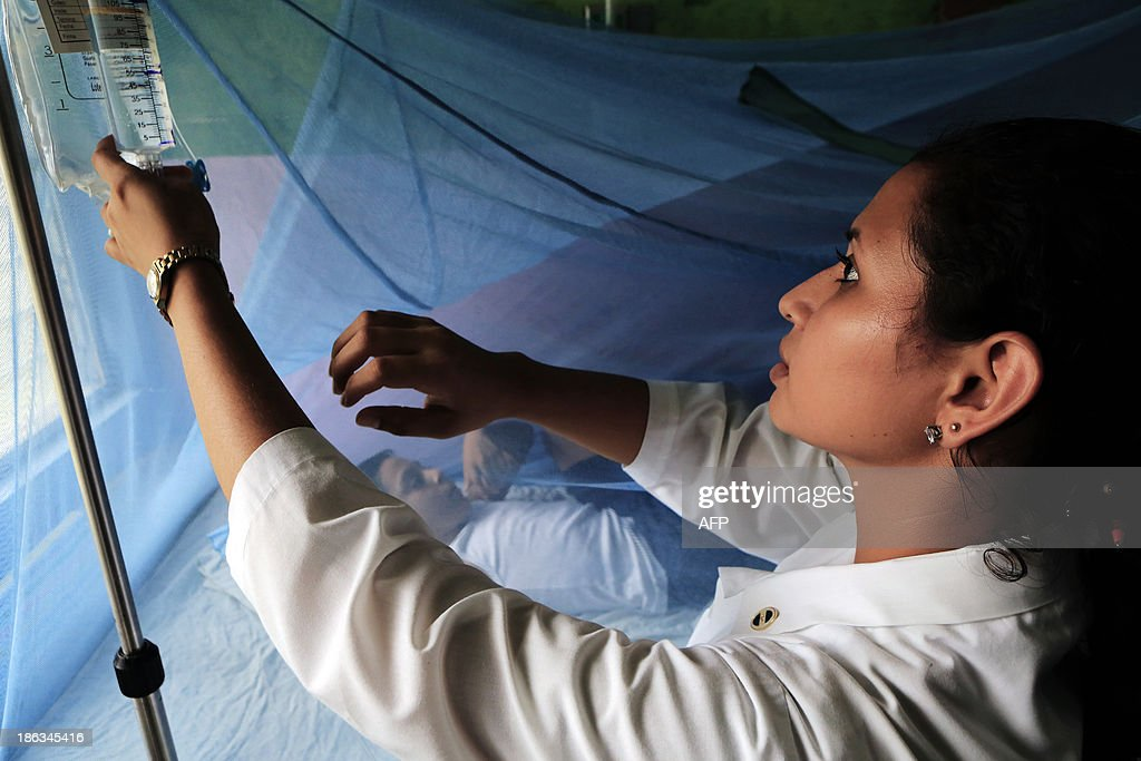 A nurse checks the fluids applied to a child suffering from dengue fever in a room of 'La Mascota' hospital in Managua, on October 30, 2013. The Nicaraguan government issued a health red alert as a dengue fever epidemic has killed 14 people so far this year and infected more than 5,000 individuals. Dengue, transmitted by the Aedes aegypti mosquito, occurs in Central America mostly during its rainy season from May to November. The disease causes fever, muscle and joint ache as well as potentially fatal dengue hemorrhagic fever and dengue shock syndrome. AFP PHOTO / Inti OCON