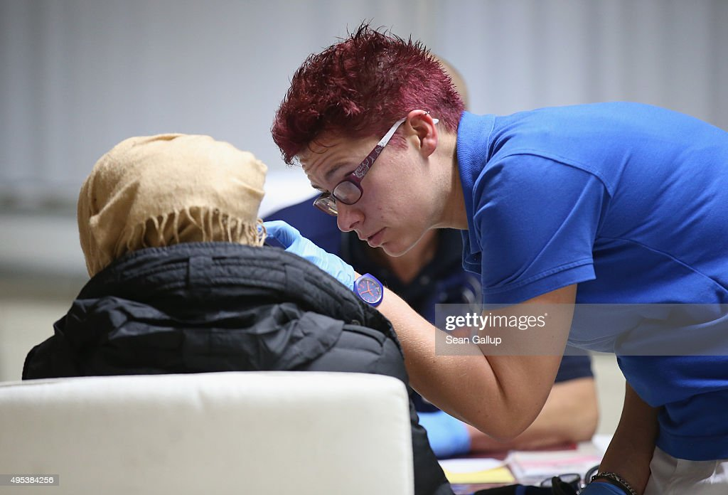 A nurse checks the temperature of an arriving migrant from Syria seeking asylum in Germany at a former office park that has become short-term accommodation for migrants on November 2, 2015 in Sumte, Germany. Sumte, a farming village located southwest of Hamburg with a population of 102, has begun receiving 500 migrants who are being housed in an abandoned office park on the village edge. The number of migrants at the shelter could reach up to 750 in coming weeks as Germany struggles to accommodate the unrelenting flood of migrants arriving at a rate of thousands per day. Authorities are distributing migrants seeking asylum in Germany at shelters nationwide, both in urban centers and in small, rural communities.