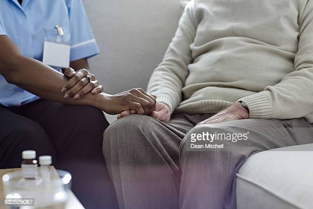 Nurse consoling senior man