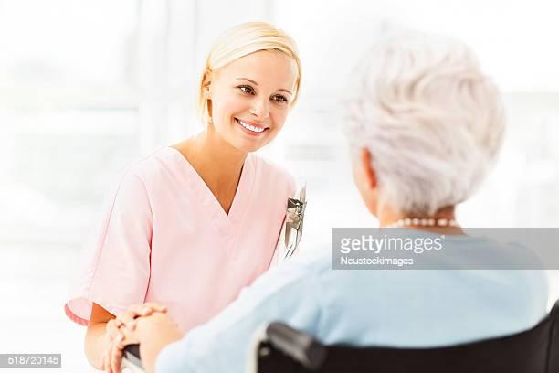 Krankenschwester Trösten Senior Patient auf Rollstuhl