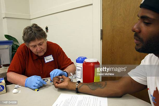 Nurse Dianne Wash takes a blood sample to check the glucose level of Keri Anderson as nurses and physicians give free basic health screenings and...